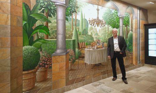 Художник Эдди Ван Хоф на фоне авторской росписи стены